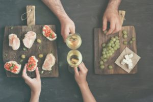 Couple drinking white wine with snacks for wine on a dark background, top view